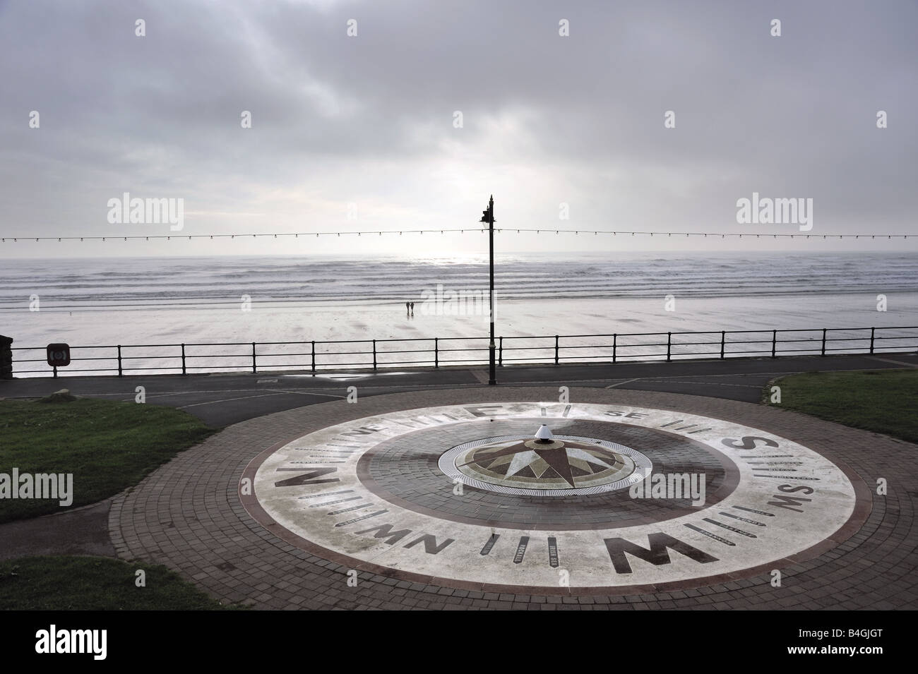 Early morning scene with compass, showing shipping forecast areas, on seafront at Filey, Yorkshire - Stock Image