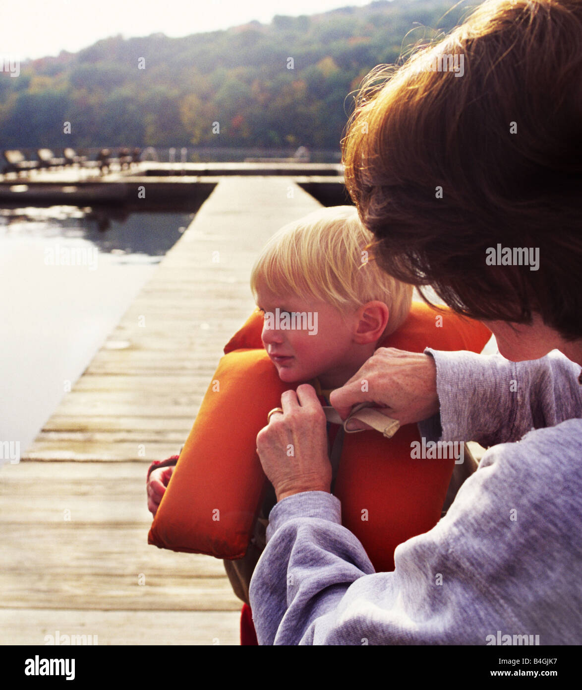 mother securing life vest on child - Stock Image
