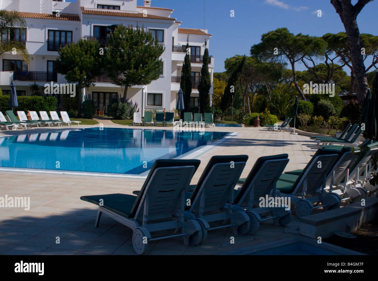 A view of the pool with loungers - Stock Image