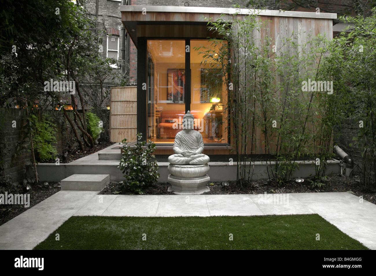 Buddha Statue In Modern Urban Garden Stock Photo Alamy