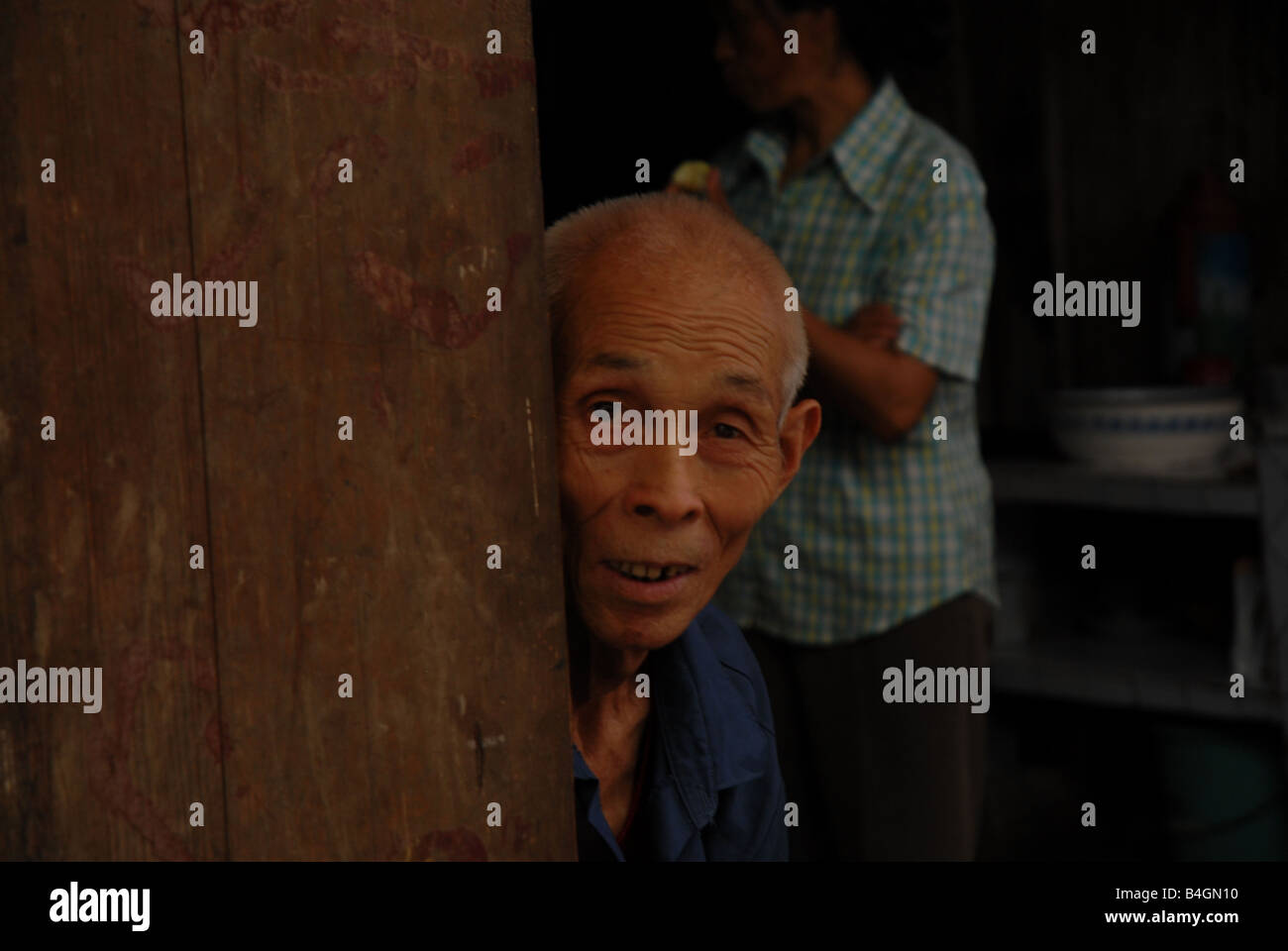 A man looks out to a buisy weekly market from the kitchen of his home in rural Gongtan Village, Chongqing Municipality, Stock Photo