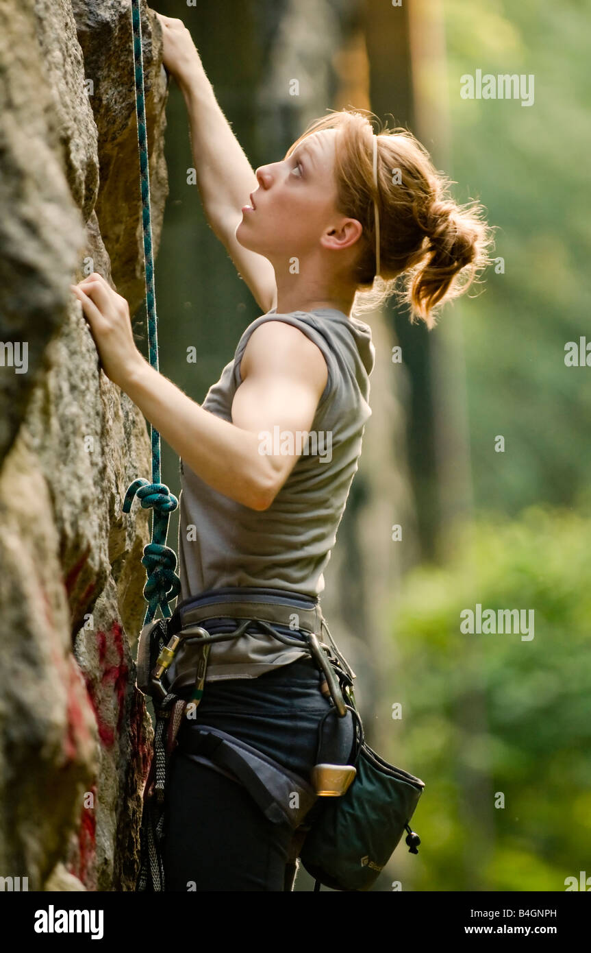 Female rock climber attempts to make her way up an old stone structure in the New England woods of Massachusetts Stock Photo