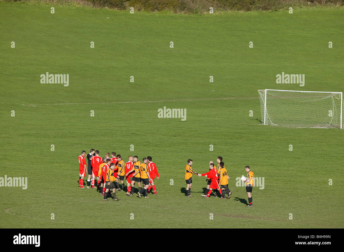 Two Sunday league football teams shake hands at the end of a game. - Stock Image