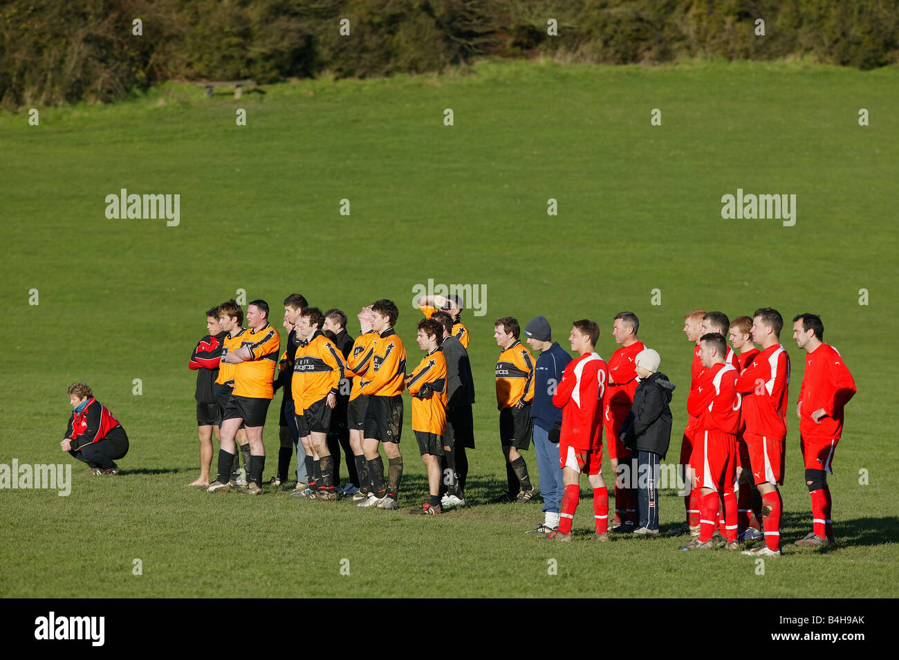 Two Sunday league football teams watch a penalty shoot out. - Stock Image