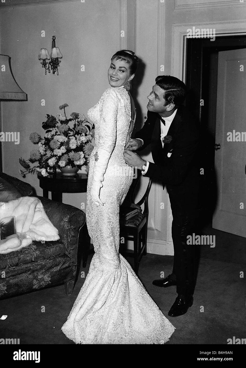 Actress Anita Ekberg has her dress zipped up by her husband Anthony Steel October 1956 - Stock Image