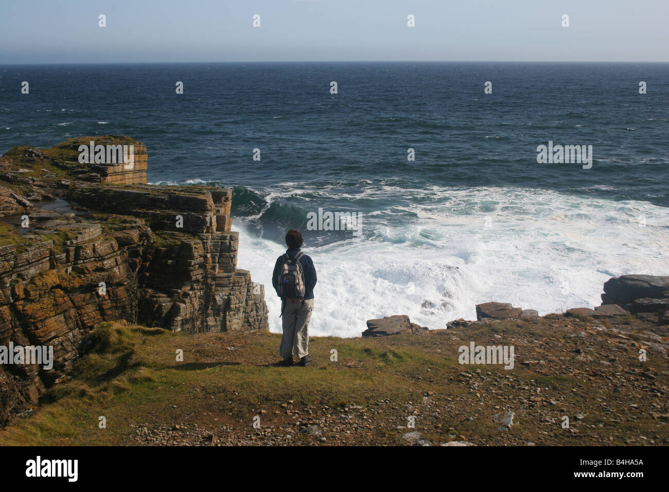 A woman walking on the coast at Deerness, Orkney Isles, Scotland - Stock Image
