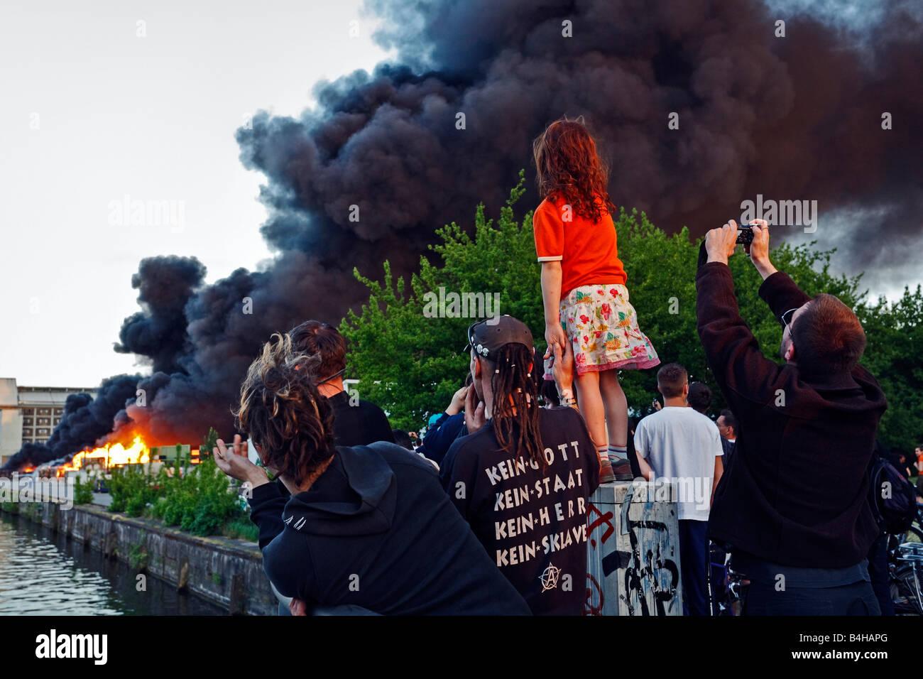People looking at burning paper mill, Kreuzberg, Berlin, Germany - Stock Image