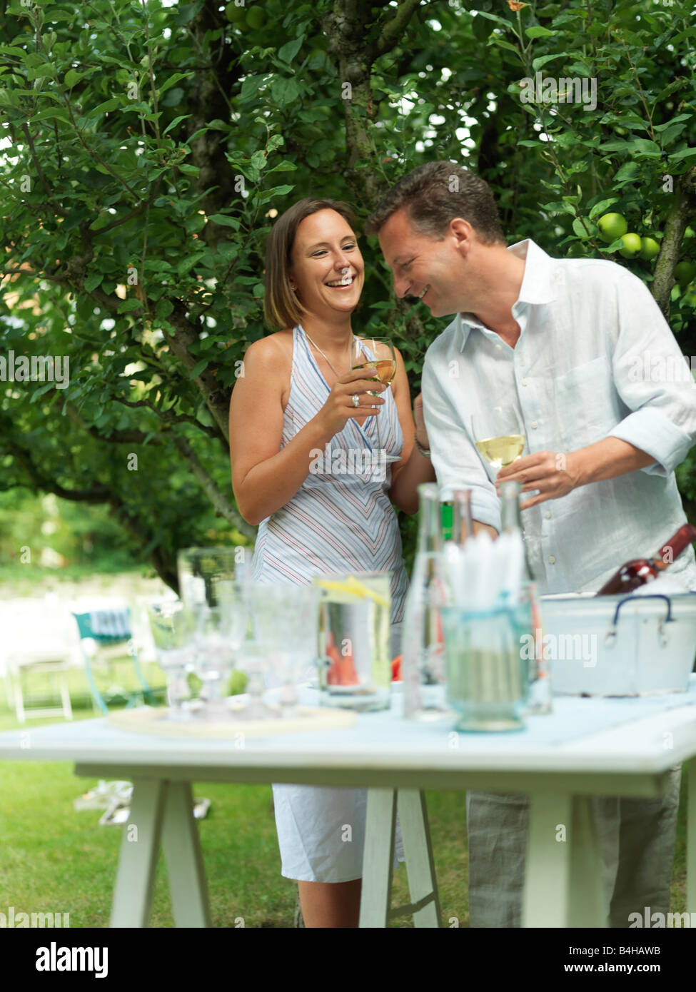 Couple holding glasses of wine and smiling in garden Stock Photo