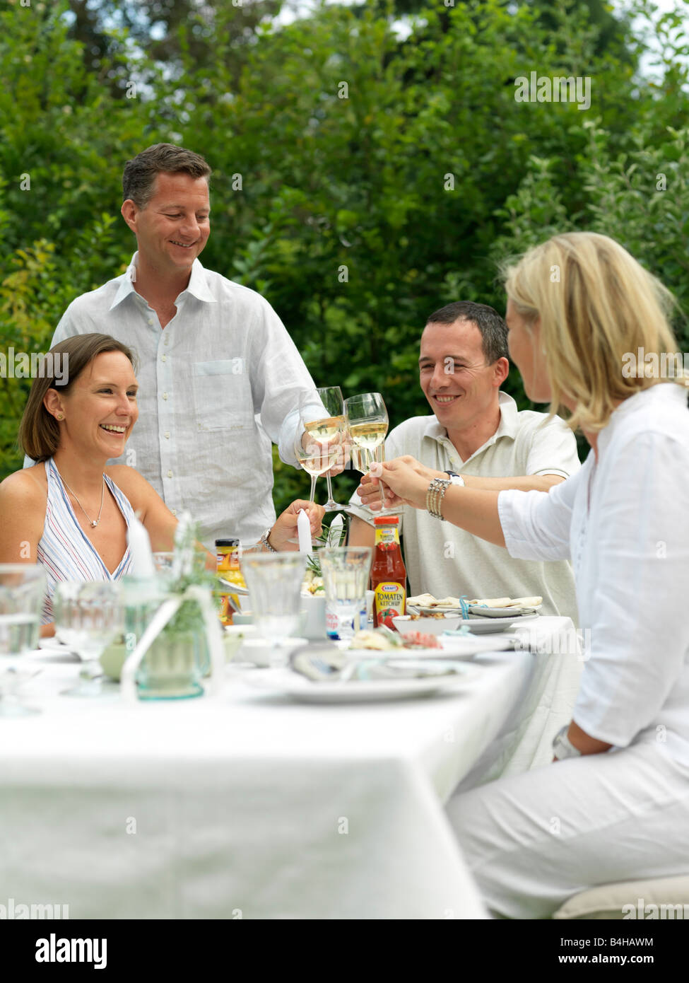 Two couples toasting with wine glasses at a garden party - Stock Image