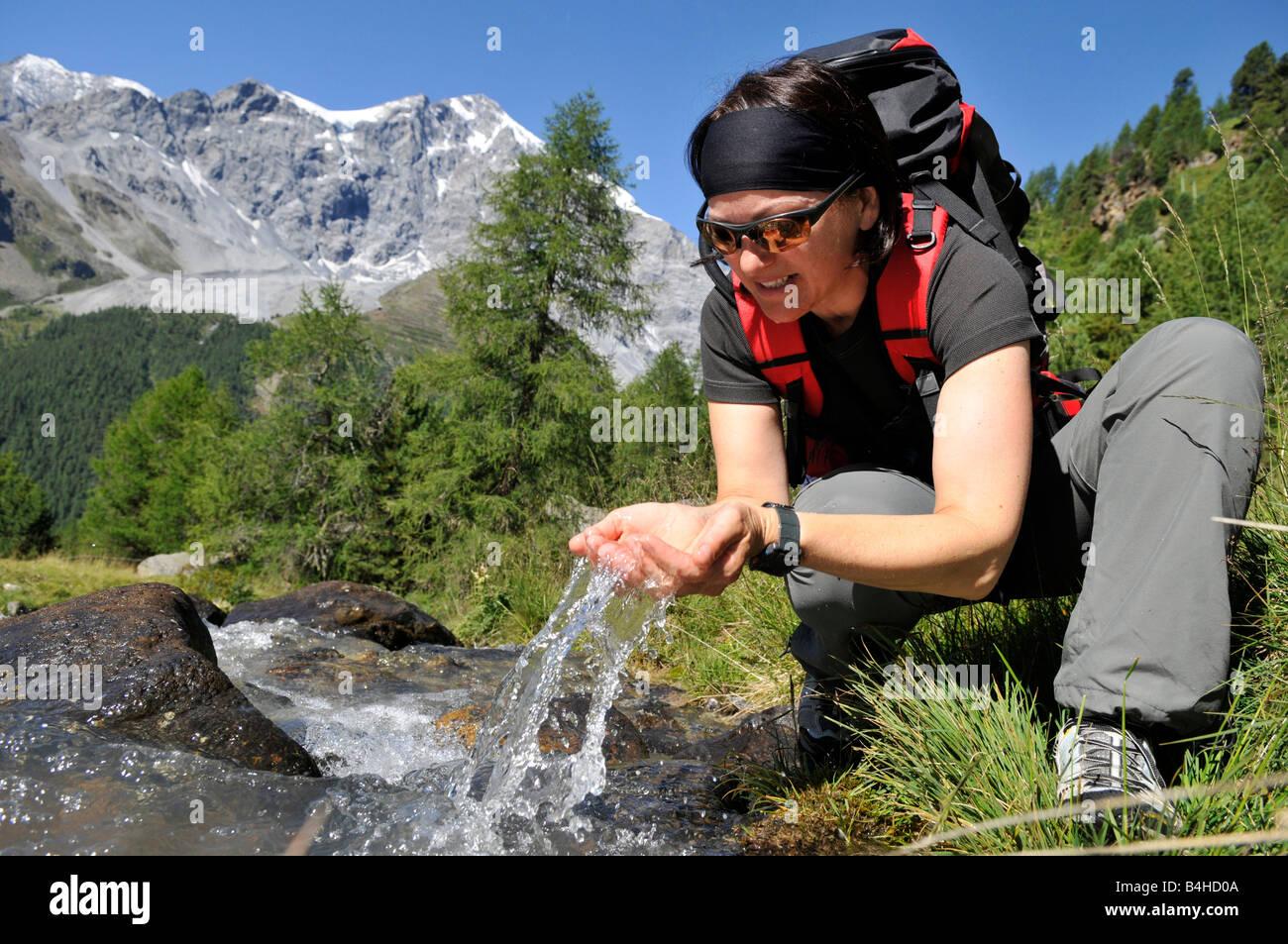 Female hiker drinking water from creek, Trentino-Alto Adige, Italy - Stock Image