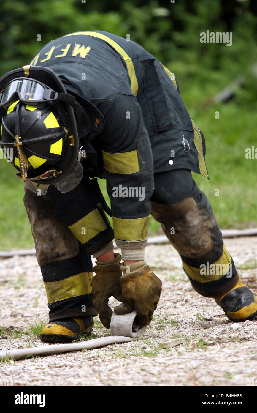 A firefighter rolling the hose after it being used at a scene - Stock Image