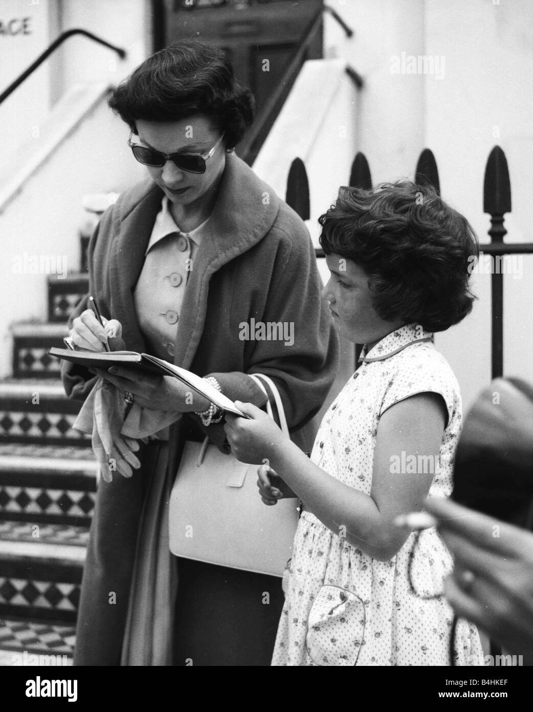 Actress Vivien Leigh signing autographs for a young fan in London August 1956 - Stock Image