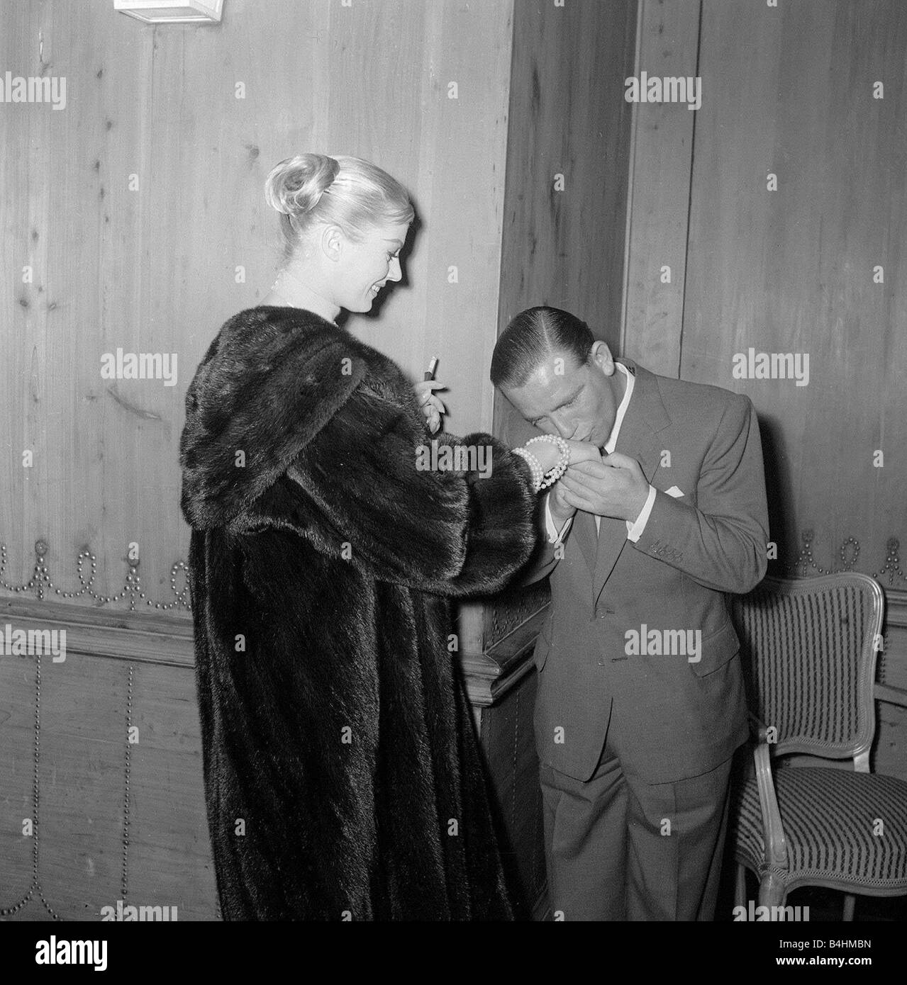 Actor and comedian Norman Wisdom kisses the hand of actress Anita Ekberg at the savoy Hotel May 1956 - Stock Image