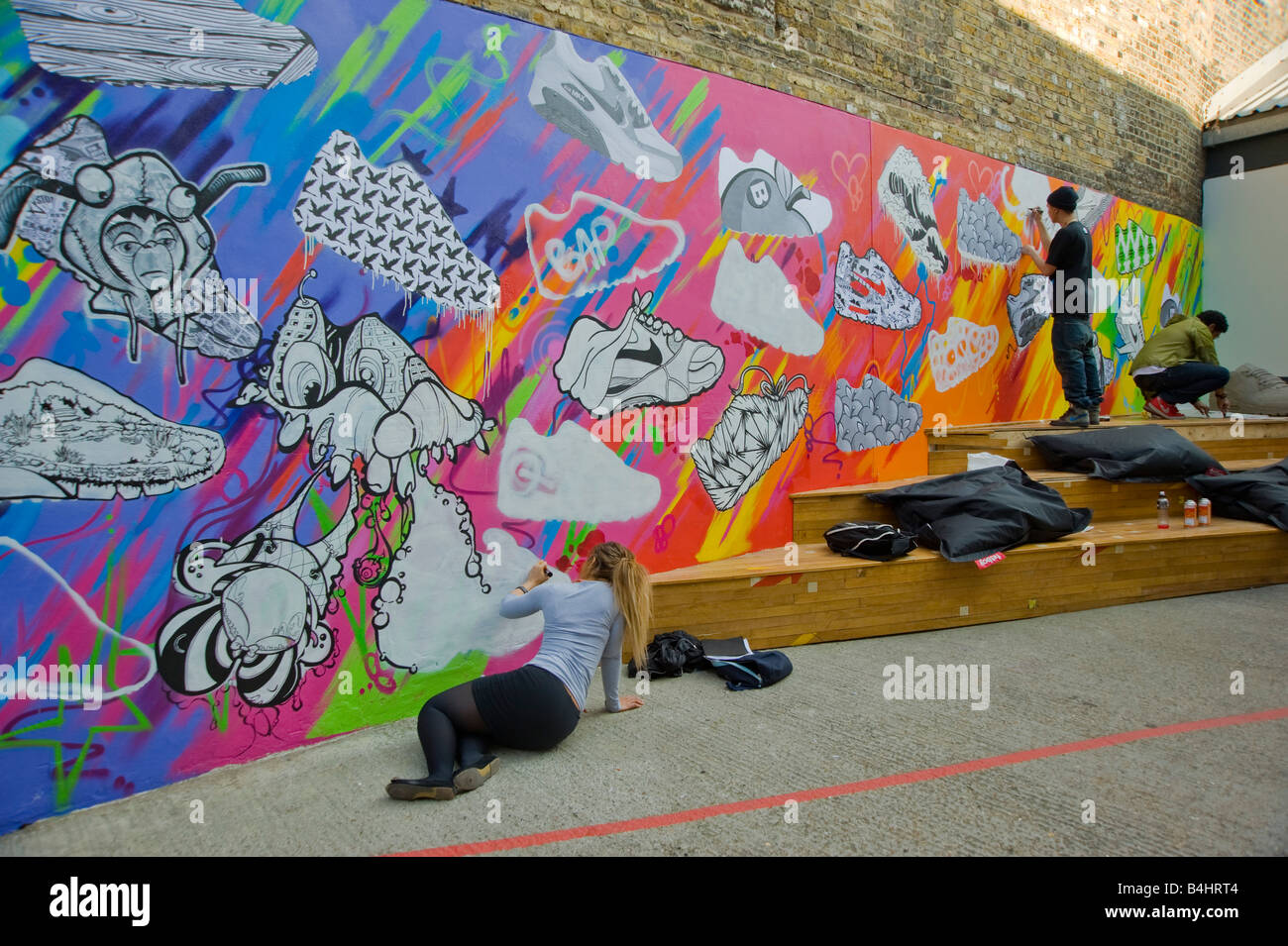 Young people painting a large mural of Nike 90 trainers on a wall at the Nike shop in Hoxton Hackney East London Stock Photo