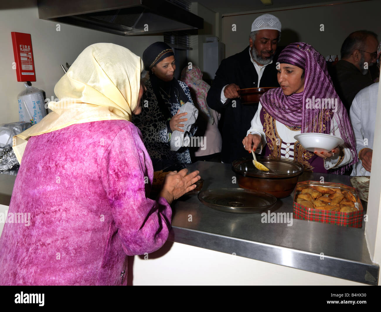 Eid Party at St Josephs Church Hall Epsom Surrey Women Serving Food which They Have Cooked and Brought From Home - Stock Image