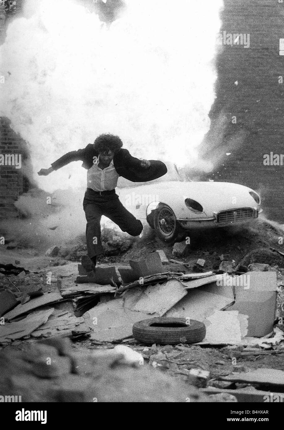 Actor Martin Shaw as Ray Doyle in The Professionals 1978 television programme running away from an exploding E Type - Stock Image