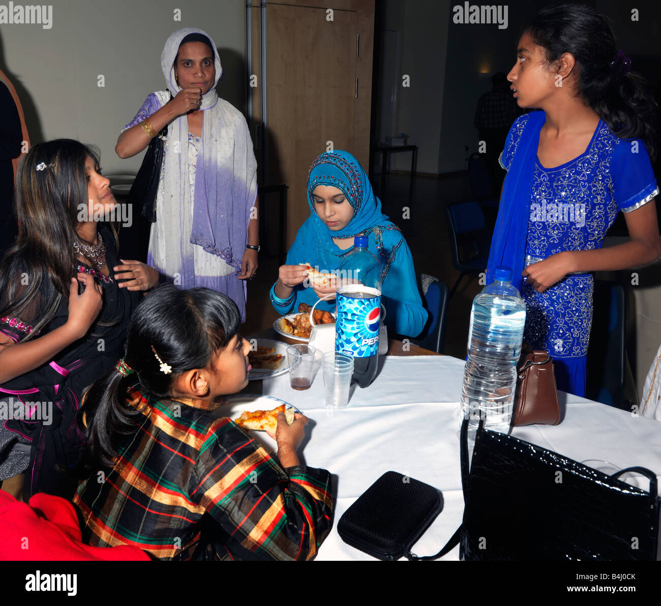 Eid Party at St Josephs Church Hall Epsom Surrey Teenage Girls Eating in the Womens Section - Stock Image