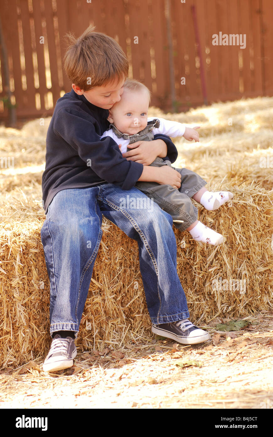 Big brother holding his baby brother at a farm - Stock Image