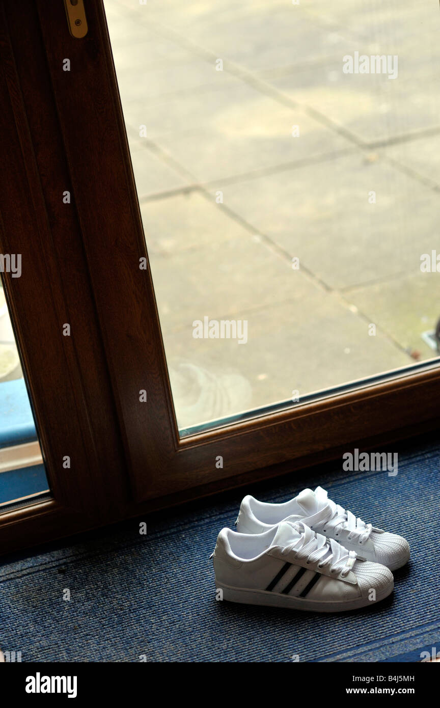 pair of new white training shoes on doormat - Stock Image