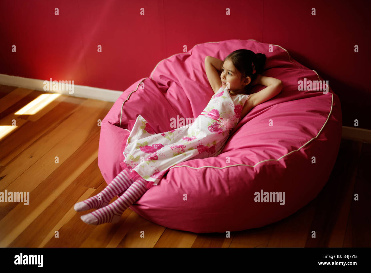 Girl 5 relaxes on pink bean bag Stock Photo