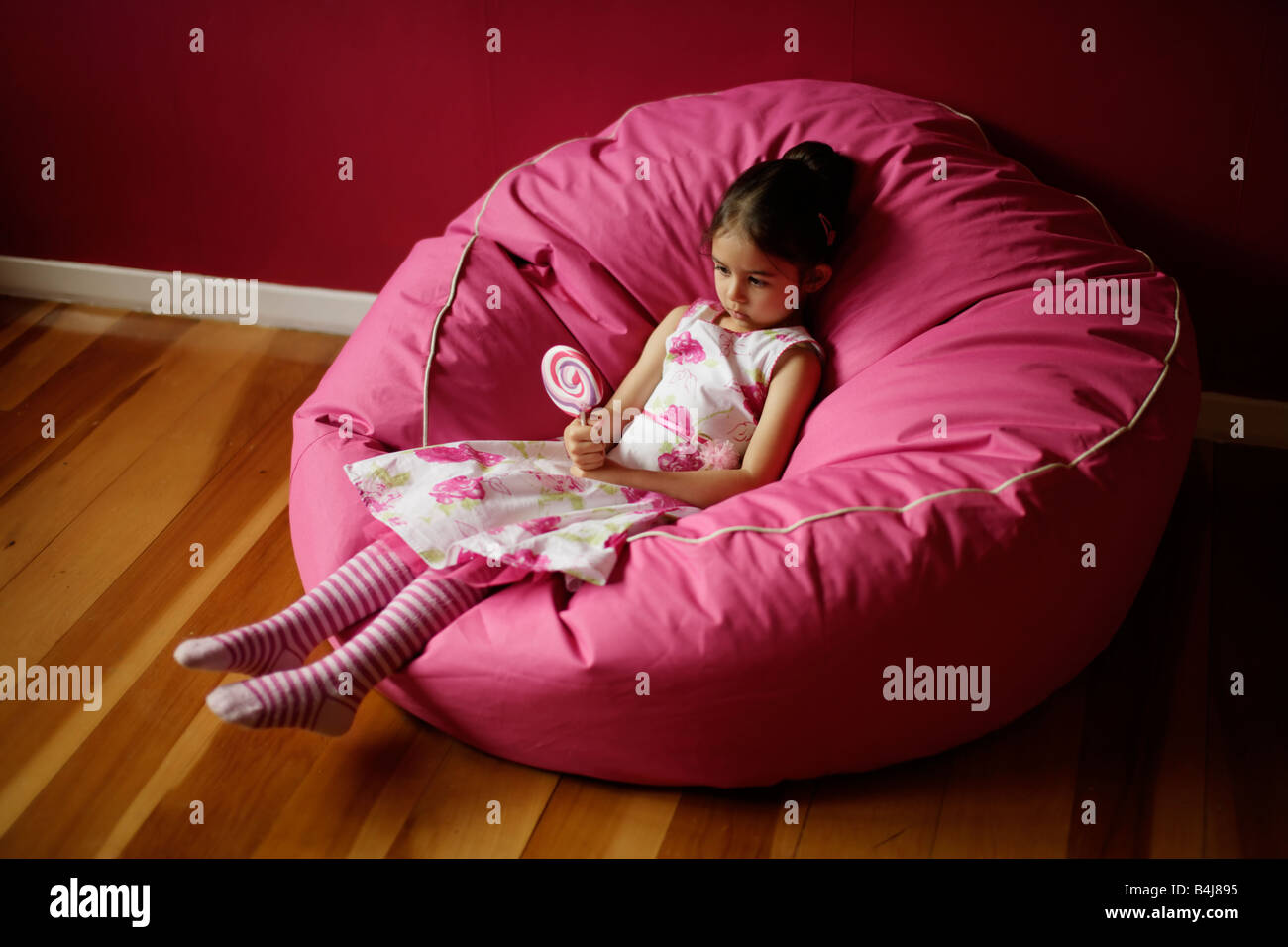 Girl 5 on pink bean bag with lollipop - Stock Image