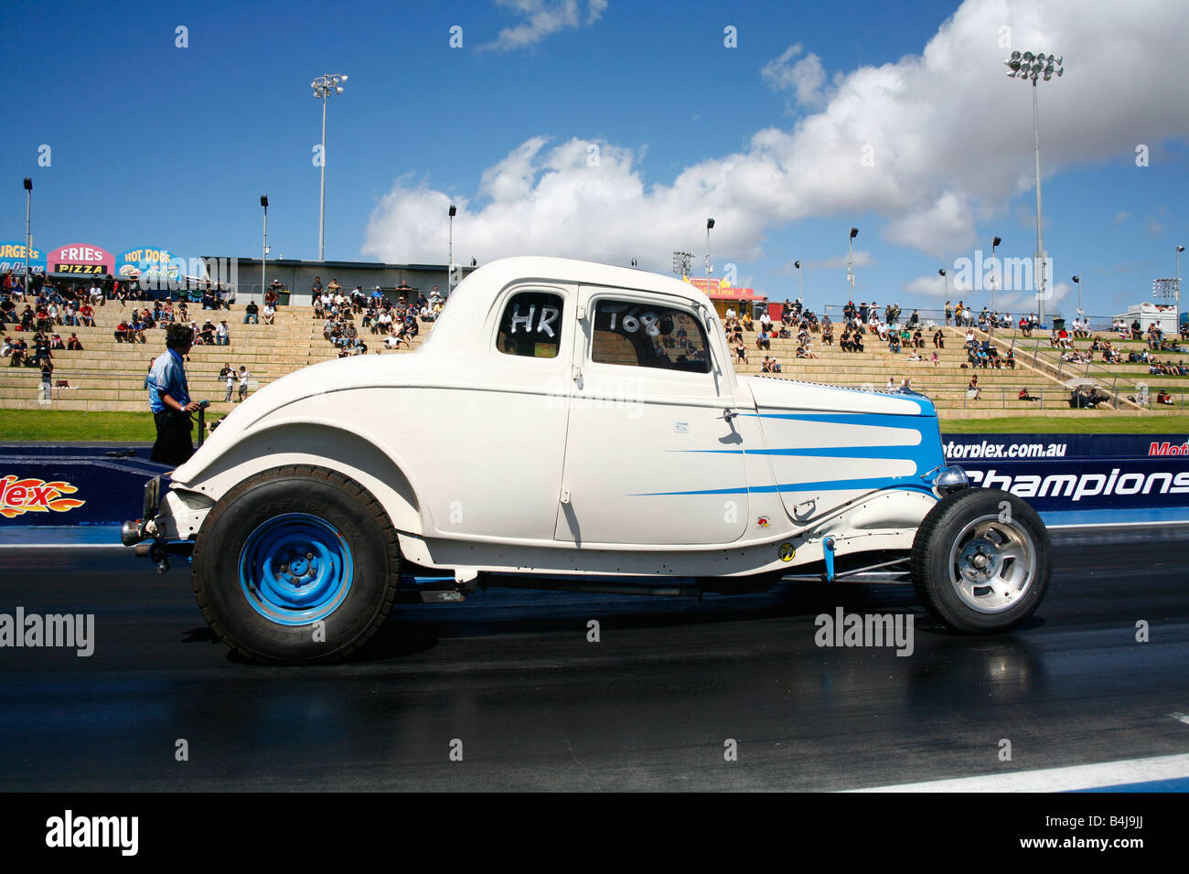 A hot rod car sitting on the start line at a drag race motorsport event - Stock Image