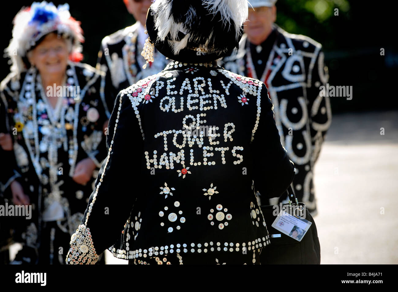 The London Pearly Kings & Queens Society: Back view of the Pearly Queen of Tower Hamlets walking towards fellow Stock Photo