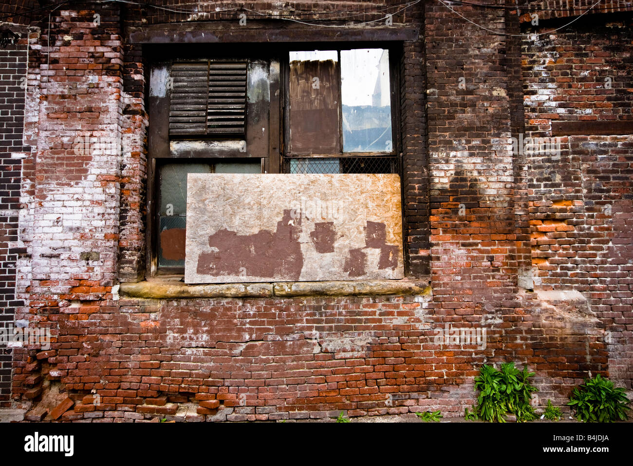 A beaten up window in the back of a factory in a brick wall in downtown Seattle, Washington. - Stock Image