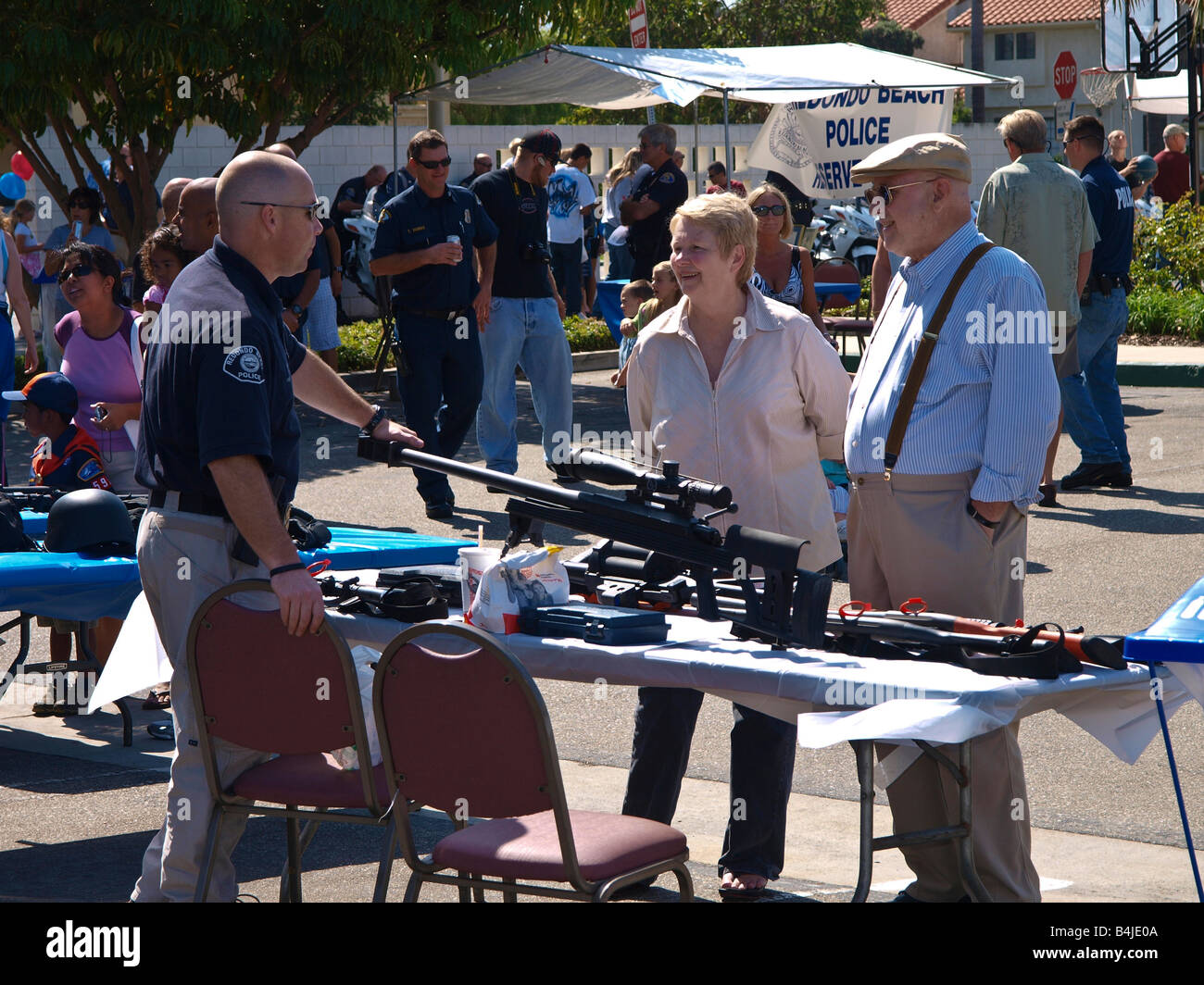 Redondo Beach police officer explains some of the weaponry used by law enforcement, to fair attendees - Stock Image