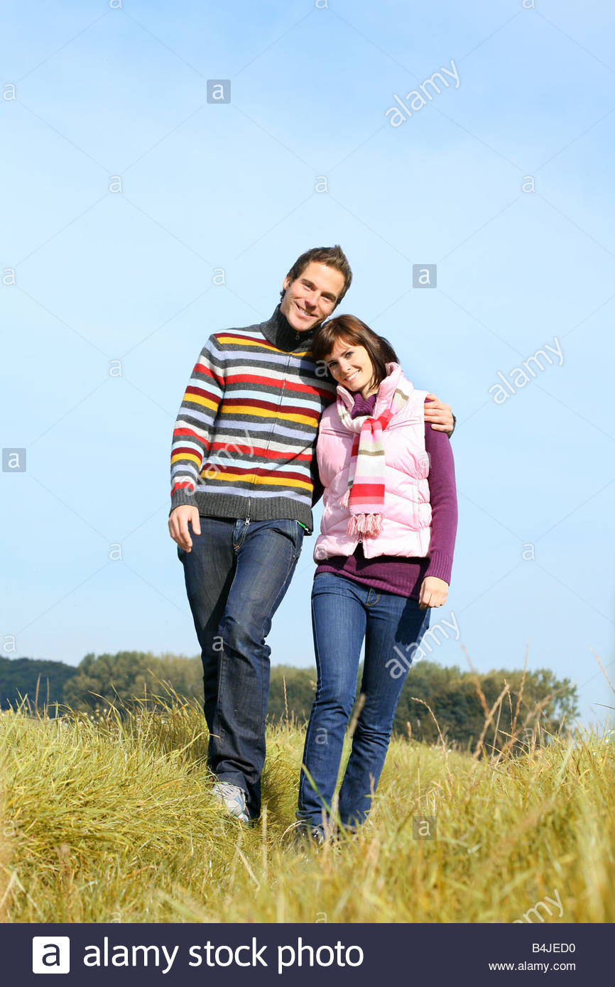 young couple walking through the landscape - Stock Image