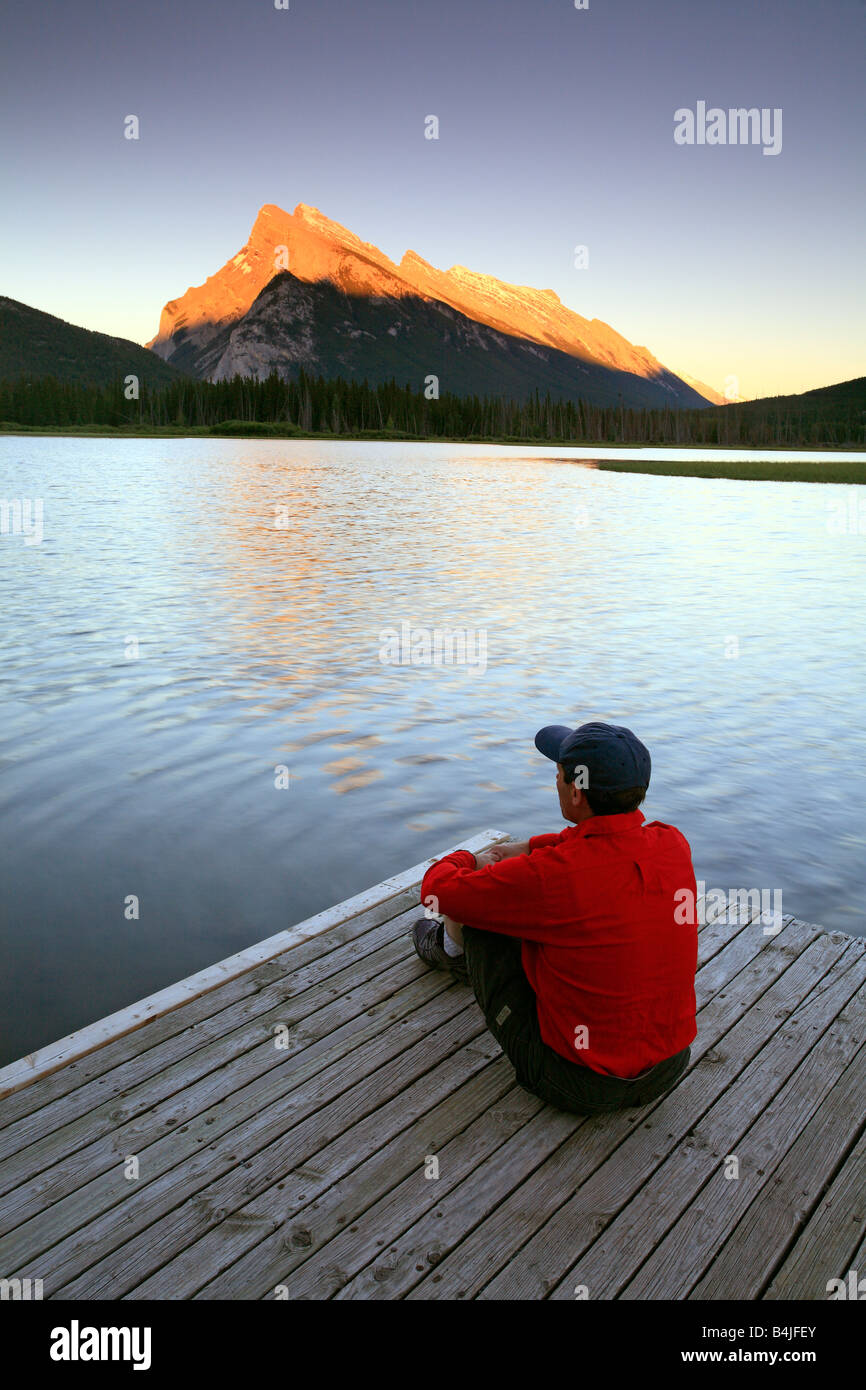 Adult male sitting on dock at Vermillion Lake with Mount Rundle sunset in Banff National Park Alberta Canada - Stock Image