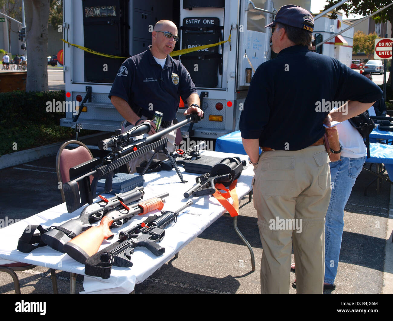 Redondo police officer explans some of the weaponry used by the Redondo Beach Police Dept Swat team at the annual - Stock Image