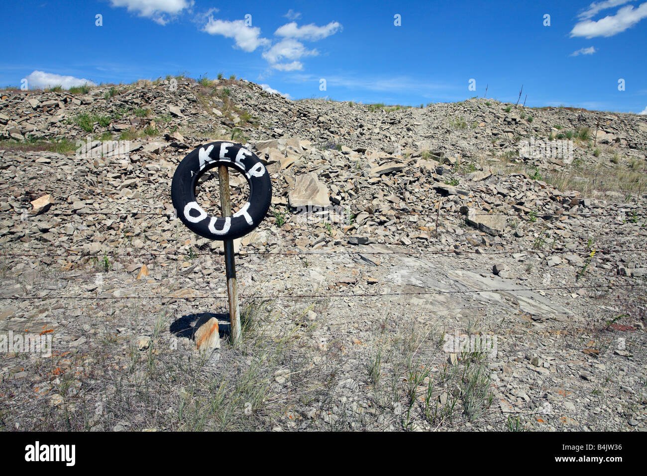 Barbed wire fence with tire sign painted keep out near Pincher Creek Alberta Canada - Stock Image