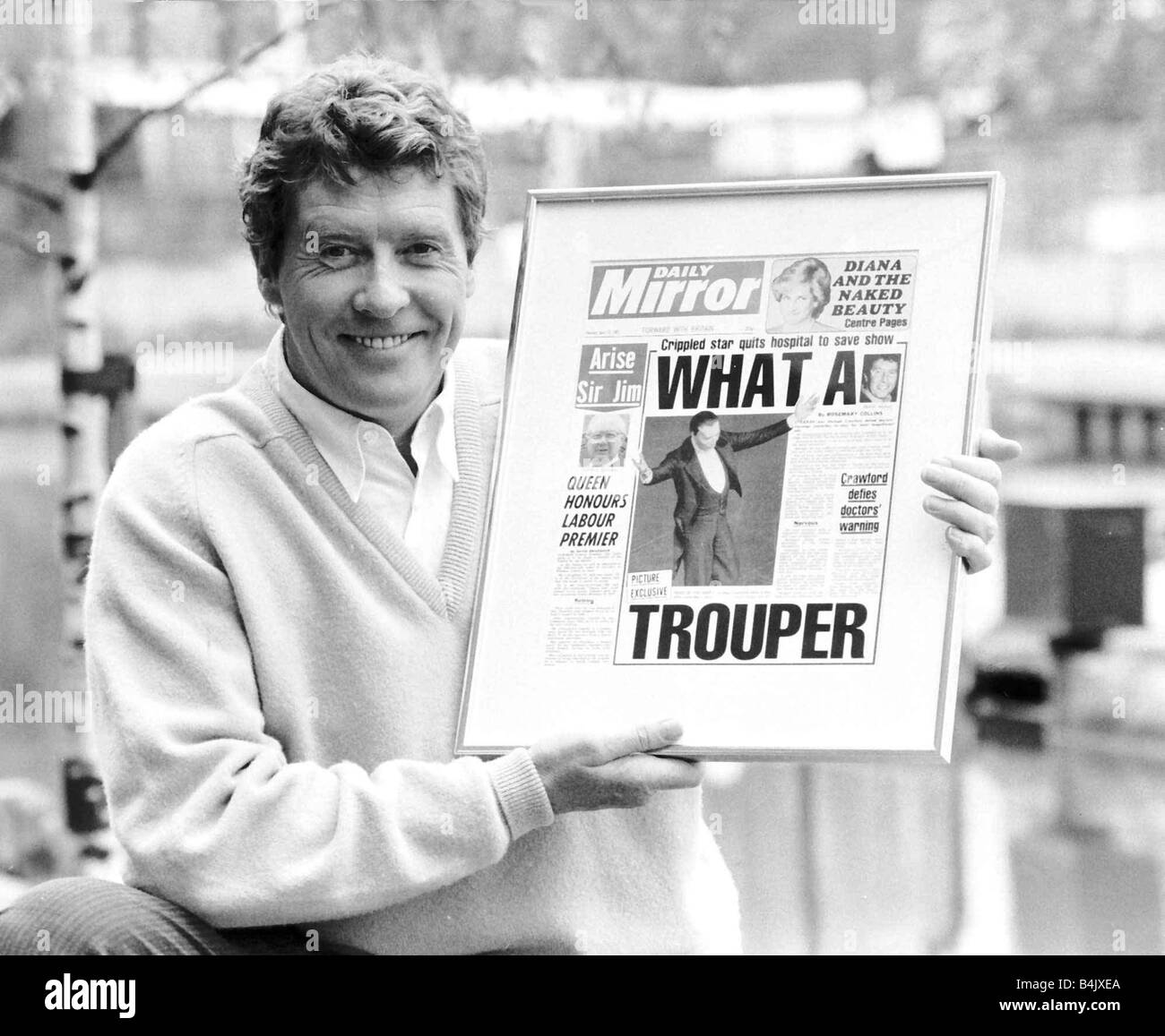 Michael Crawford holds up a framed front page of the Daily Mirror June 1987 dbase - Stock Image