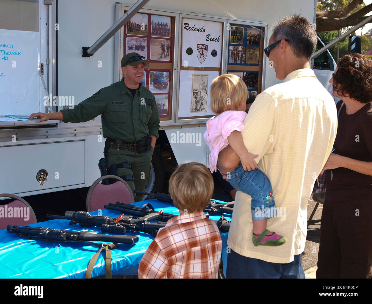 Redondo Beach swat team officer chats with fair attendees viewing some of the teams weaponry - Stock Image