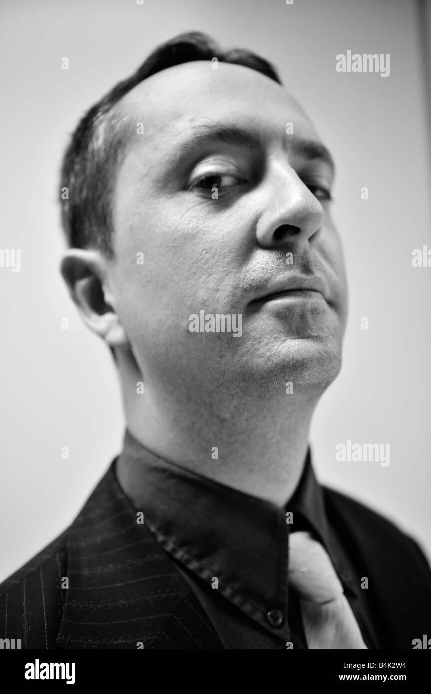 portrait man guy black white head hair dark shirt caucasian white - Stock Image