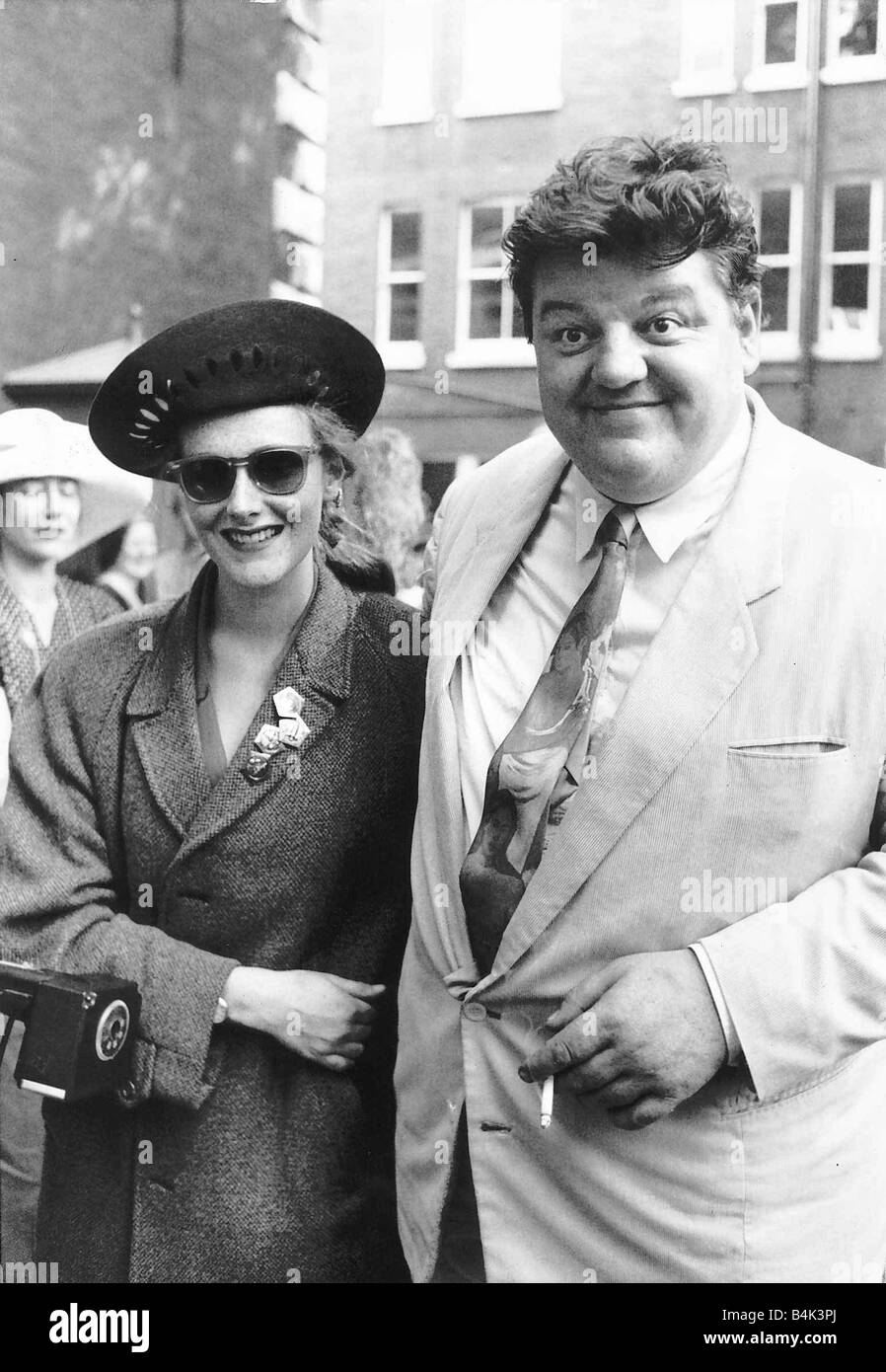 Robbie Coltrane actor arriving with unknown lady for the wedding of Nigel Planer August 1989 dbase - Stock Image