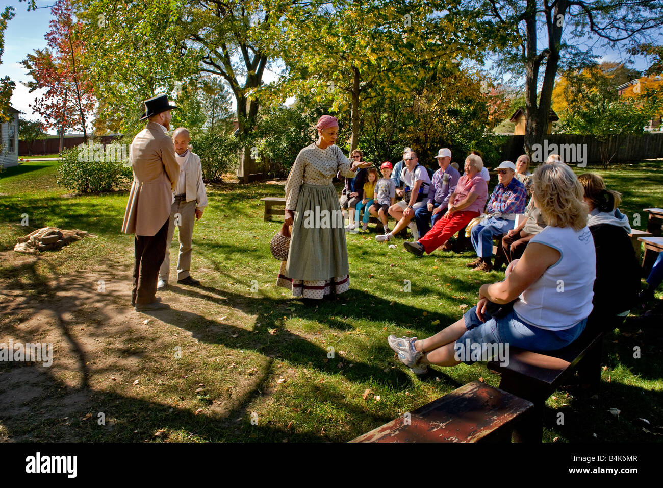 Performers in period costume act out pre Civil War slave tales at a replica of slave quarters at Greenfield Village - Stock Image