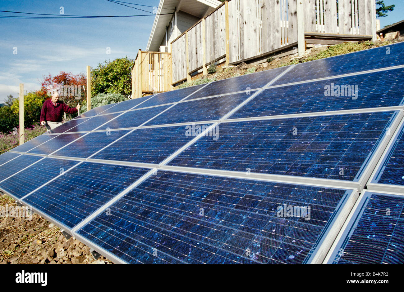 Homeowner inspecting newly installed solar panels. - Stock Image
