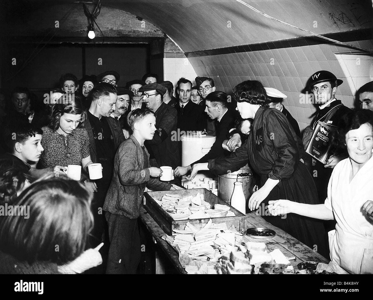 Womens Voluntary Service serve tea and sandwiches to people in an underground air raid shelter during WW2 food supply - Stock Image