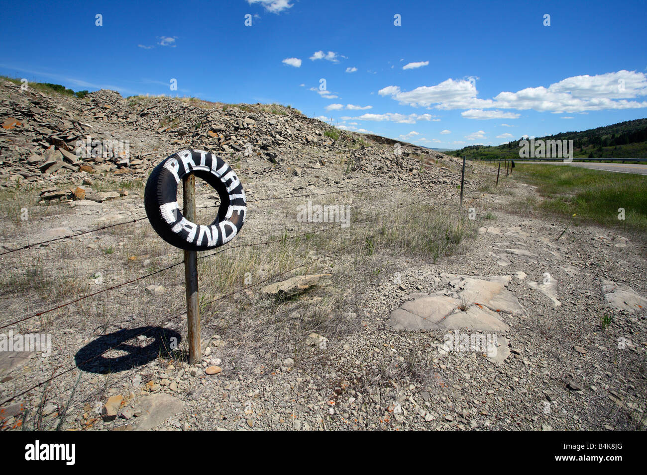 Barbed wire fence with tire sign painted private land near Pincher Creek Alberta Canada - Stock Image