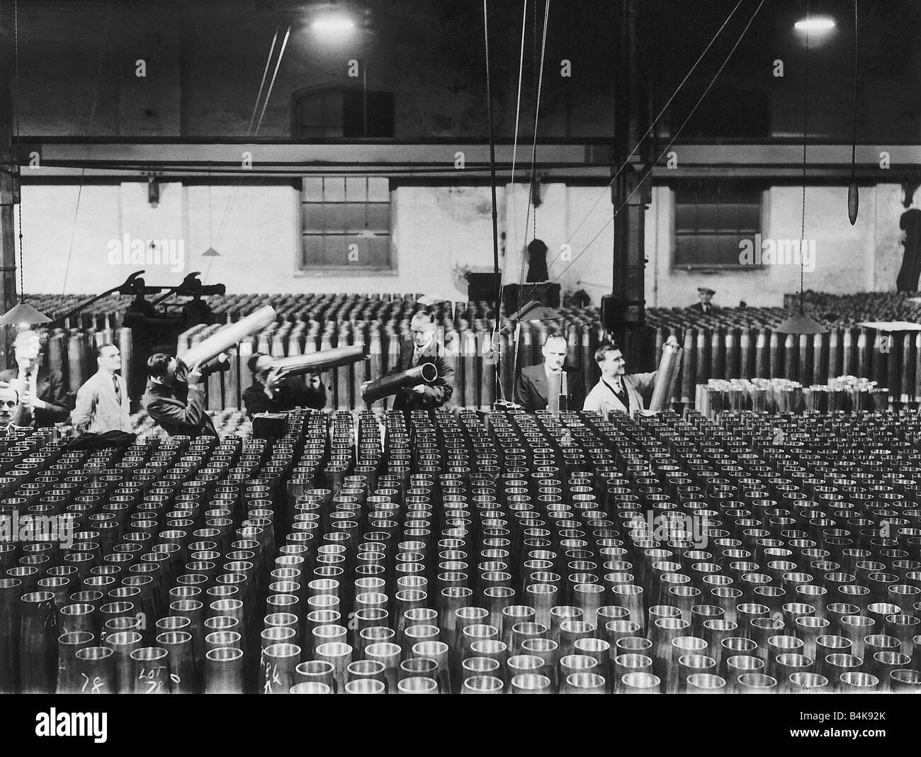 Inspectors check the quality of shells for naval guns in a munitions factory during WW2 1939 world war two - Stock Image