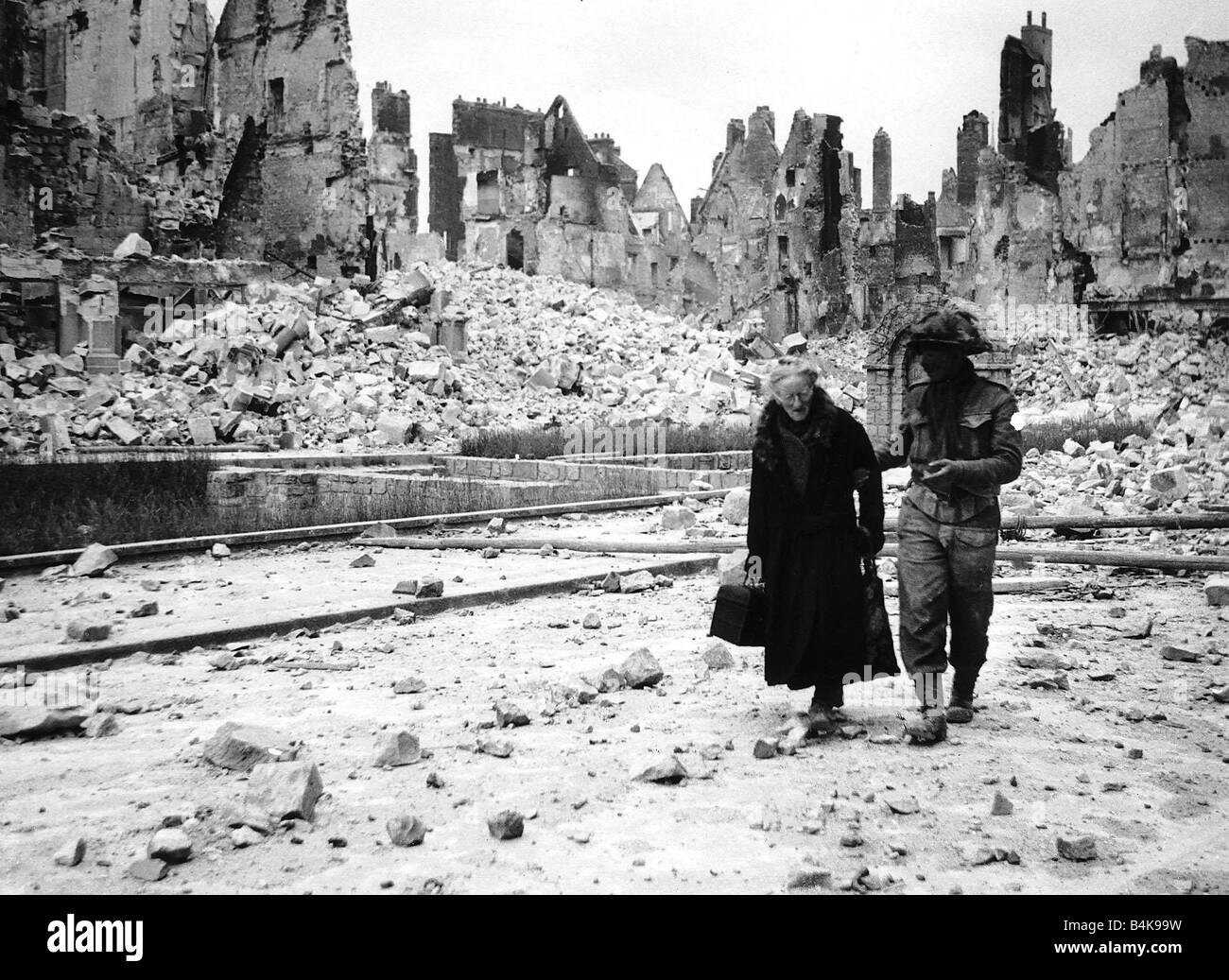 WW2 Invasion of Caen in France A soldier helps an elderly woman through the ruins - Stock Image