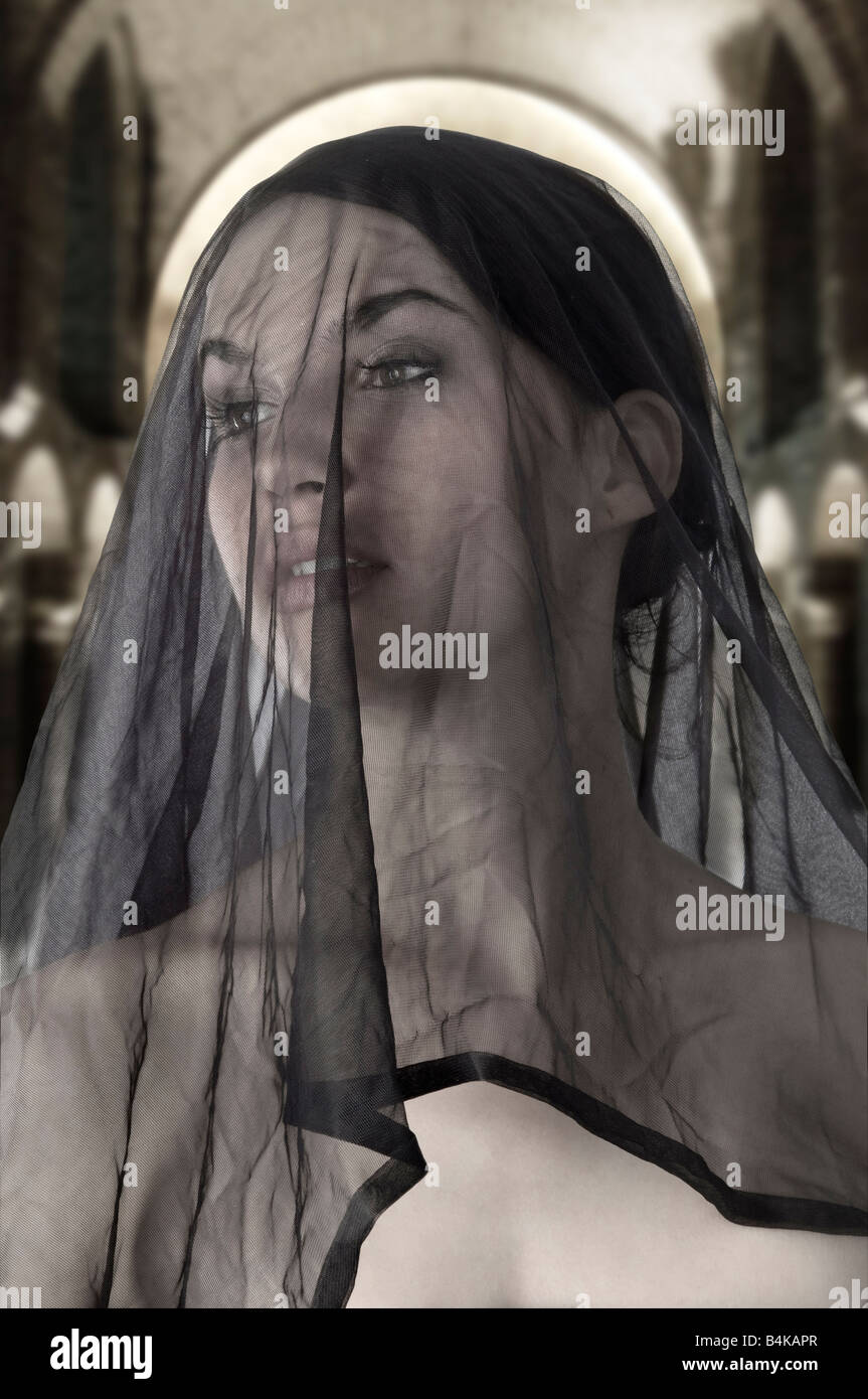 attractive widow with a black transparent veil on face - Stock Image