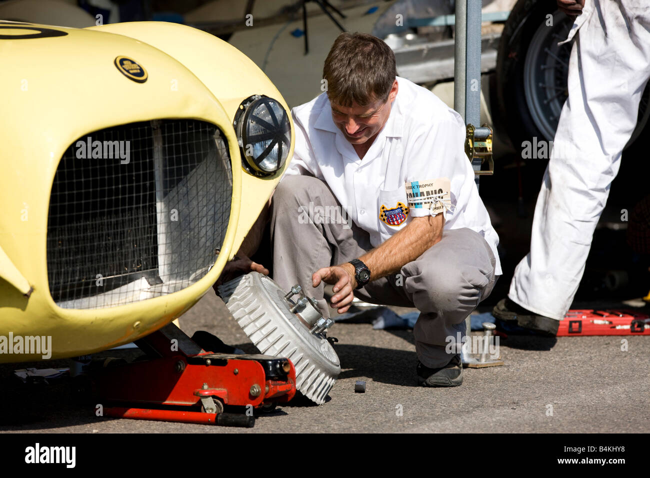 mechanic working on classic racing car at goodwood revival - Stock Image