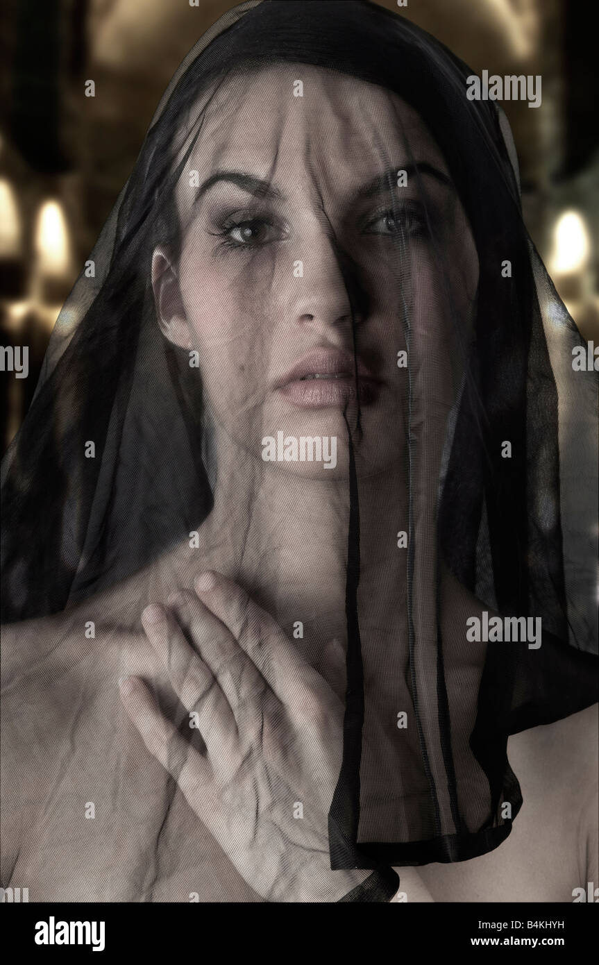 cute woman with a black transparent veil on face like a sicilian widow - Stock Image