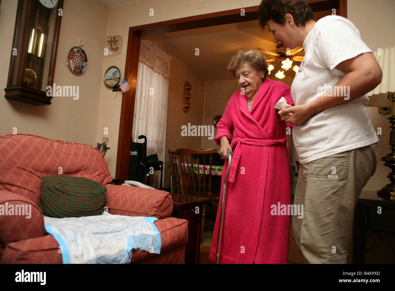 A live-in home health aide assists an elderly woman in her home ...