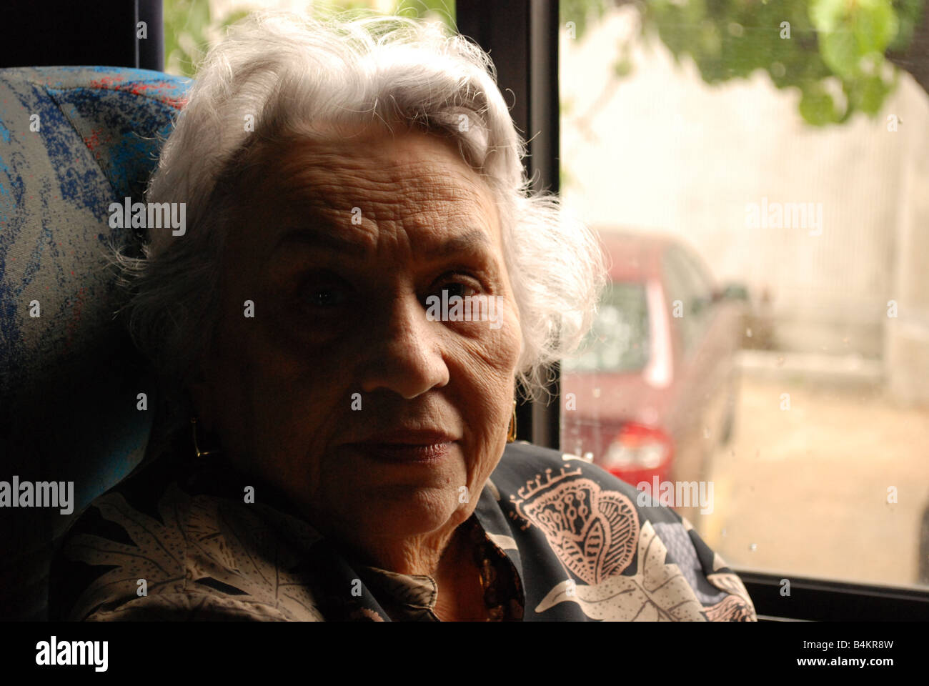 A grandmother, of white hair, looks straight while she waits for her next destiny. - Stock Image