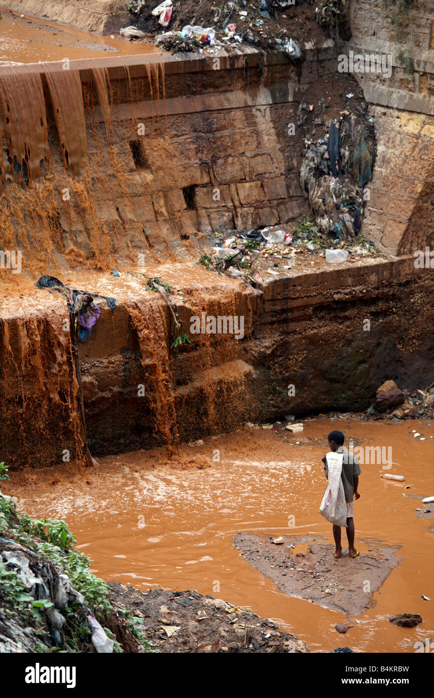 A boy looks for plastic in a polluted river, Ethiopia - Stock Image