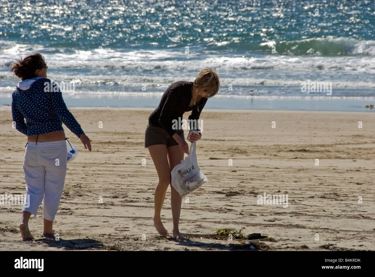 2 Women 20's Picking up Beach Trash balboa peninsula newport beach, orange county, california, ca usa - Stock Image